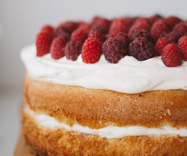 Fluffy sponge cake with cream and raspberries